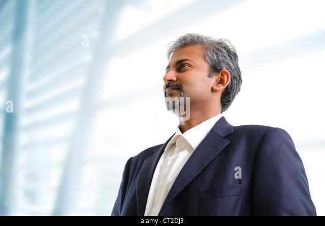 Mature Asian Indian businessman looking away standing on office background - Stock-Bilder