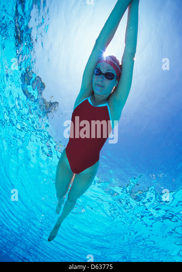 Full length of female swimmer in United States with rms raised swimsuit swimming in pool - Stock Image