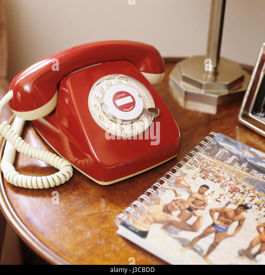 A red Art Thang vintage phone on side table with note book - Stock Image