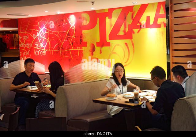 Beijing China The Malls at Oriental Plaza Pizza Hut restaurant inside interior Asian woman man tables decor - Stock Image