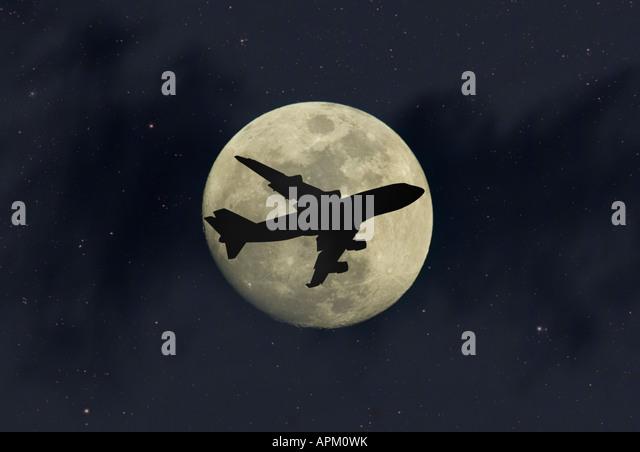 Night Flight plane flying across moon - Stock Image