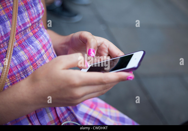 Young girl,with painted nails sends message on touch screen smart phone-close-up - Stock Image