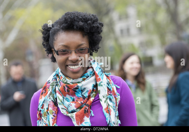 A group of people in a city park A young woman smiling wearing a purple shirt and floral scarf - Stock Image