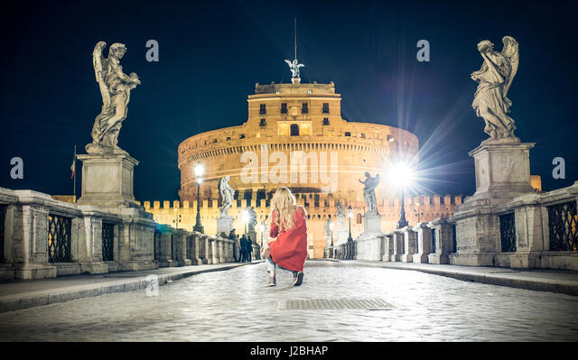 A girl is taking pictures to Castel Sant'Angelo on the Ponte Sant'Angelo bridge crossing the river Tiber - Stock Image