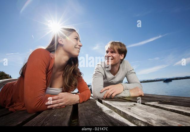 Germany, Bavaria, Couple lying on jetty at Lake Starnberg - Stock Image