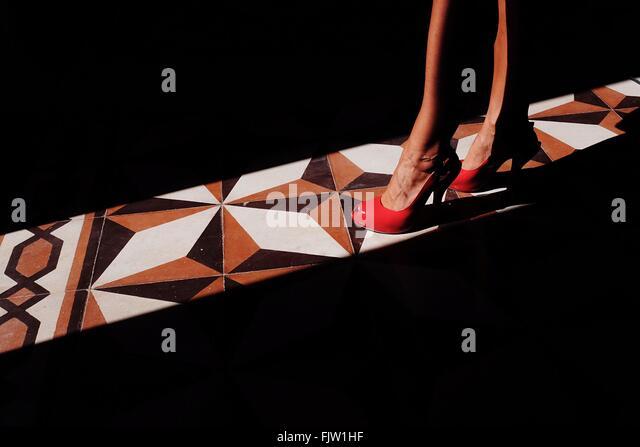 Low Section Of Woman Standing On Sunlight Over Tiled Floor - Stock-Bilder