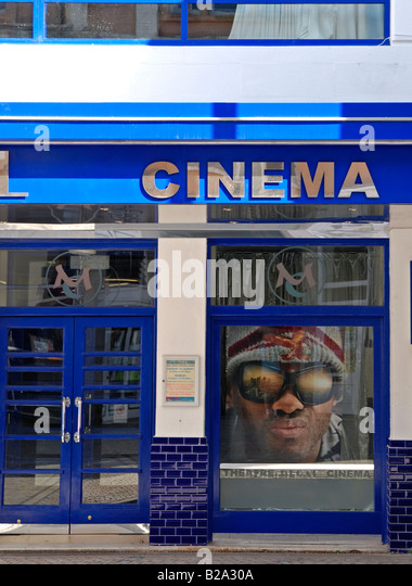 a close up of a cinema entrance door with an advert for the movie 'hancock' in the window - Stock Image