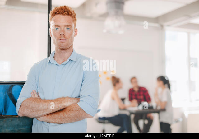 Portrait of confident young businessman standing in office with his arms crossed and colleagues meeting in background. - Stock Image