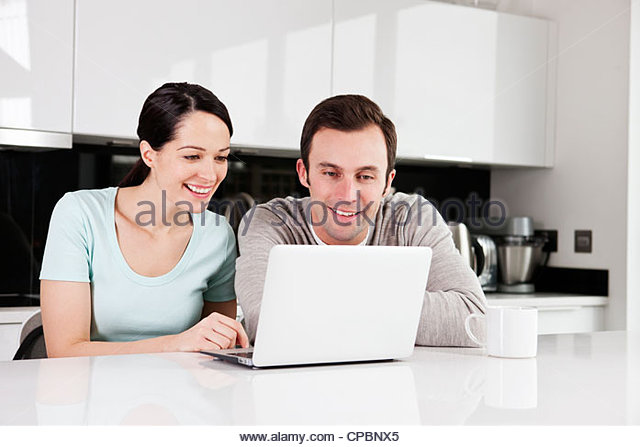 A young couple in the kitchen looking at a laptop - Stock-Bilder