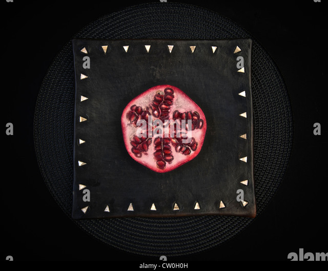 Sliced pomegranate on decorative board - Stock Image