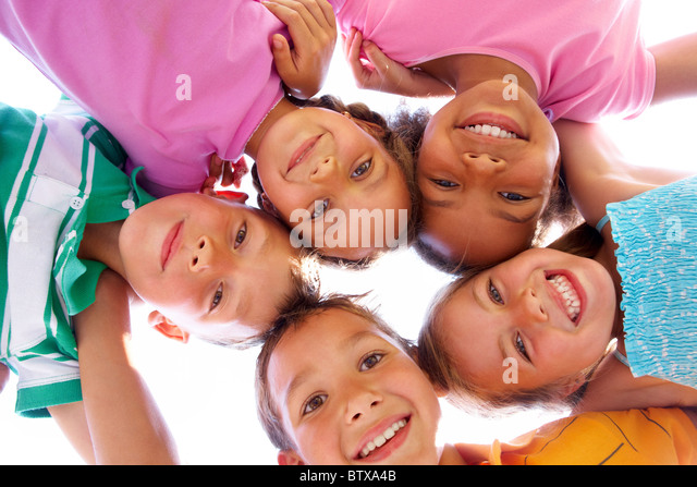 Below view of happy children embracing each other and smiling at camera - Stock Image
