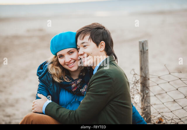 young couple sitting and posing on the beach in autumn - Stock-Bilder