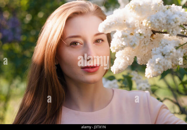 Beautiful woman with flowers of lilac Skincare - Stock Image
