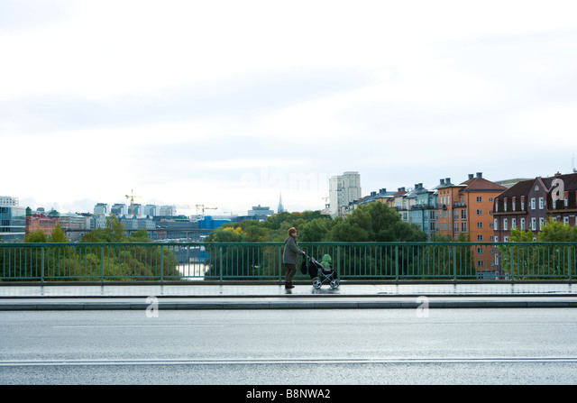 Sweden, Stockholm, woman pushing baby stroller across bridge - Stock Image