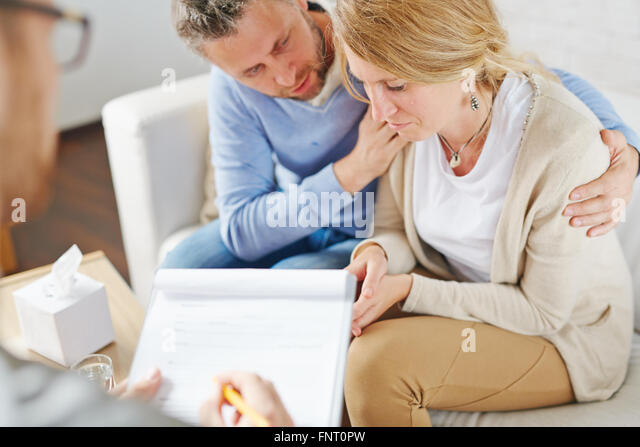 Crying woman visiting psychologist with her husband - Stock Image