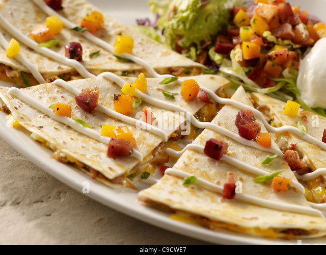 A carnitas quesadilla topped with salsa and served with sour cream and guacamole - Stock Image