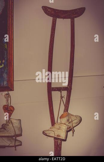 Baby pilgrim shoes and crutch  in Chapelle Saint-Thibaut, Marcourt, Belgium - Stock Image