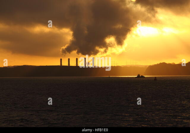 Power station on the coast at sunrise.  Global warming concept - Stock Image
