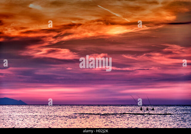 Three fishermen waiting for fishes during sunset in Indonesia - Stock Image