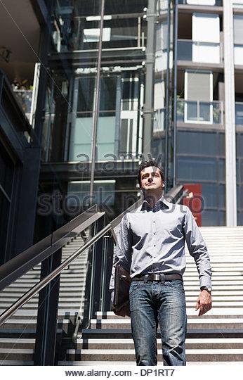 Businessman walking down stairway - Stock-Bilder
