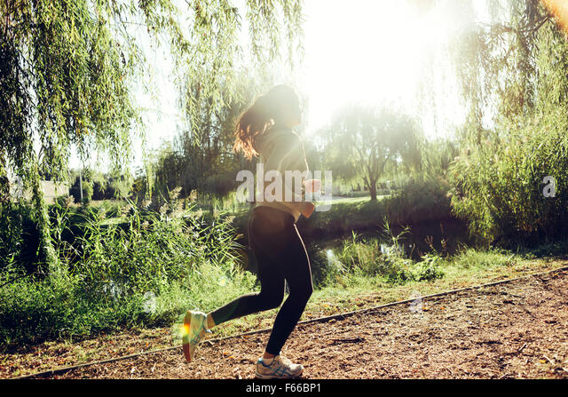 Fit beautiful woman jogging in park and staying healthy - Stock Image
