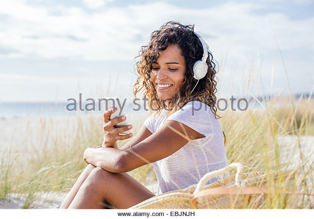Young woman selecting music for headphones in beach dunes, Tuscany, Italy - Stock Image