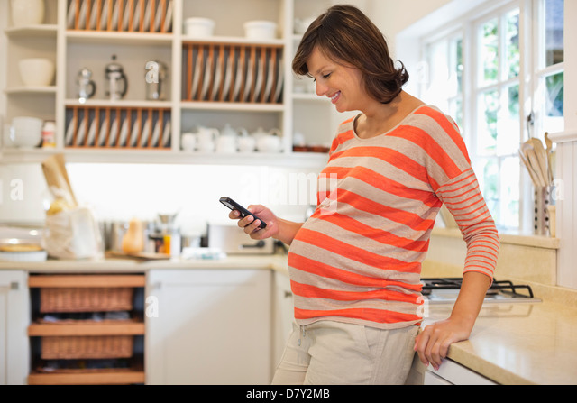 Pregnant woman using cell phone - Stock Image