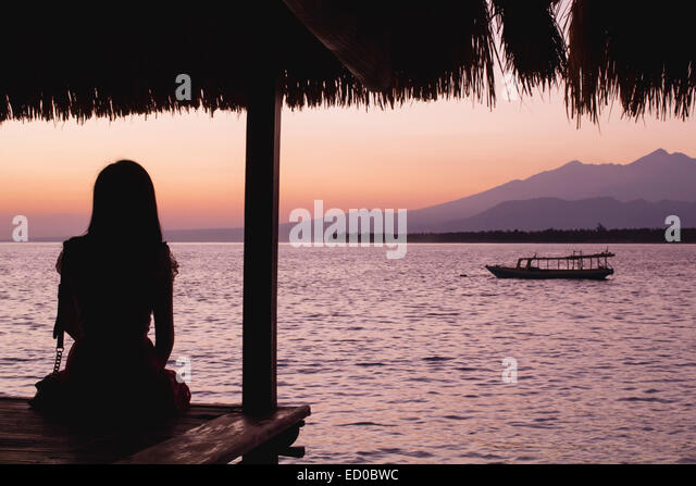 Woman looking at sunrise over Rinjani volcano, West Nusa Tenggara, Indonesia - Stock Image