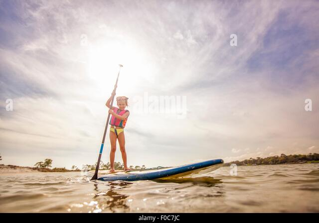 Girl standup paddleboarding in the sound, Fort Walton, Florida, USA - Stock-Bilder