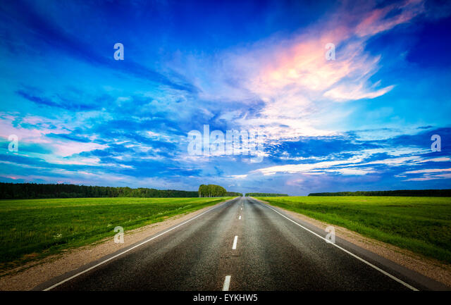 Travel concept background - road and stormy dramatic sky on sunset - Stock-Bilder