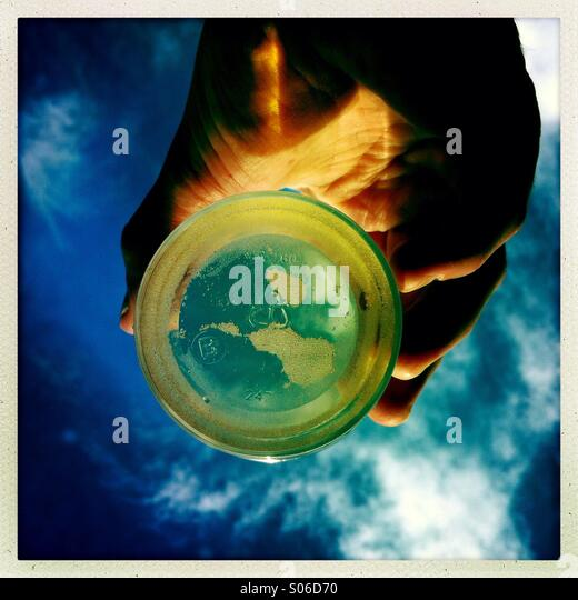 A looking up shot a hand holding a glass with liquid in it. - Stock-Bilder