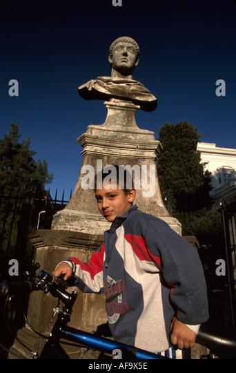 Italy Rome Villa Borghese Park Viale dei du Sarcofaghi boy resident bicycle Roman bust art statue - Stock Image