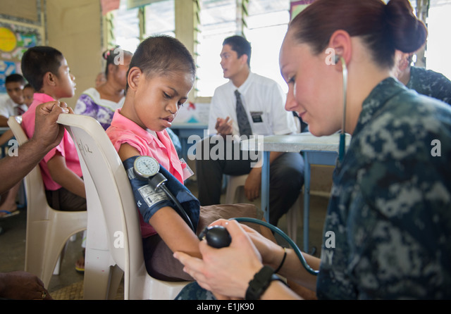 U.S. Navy Hospital Corpsman 3rd Class Tara Macdonald, right, checks the vital signs of a child being screened to - Stock Image