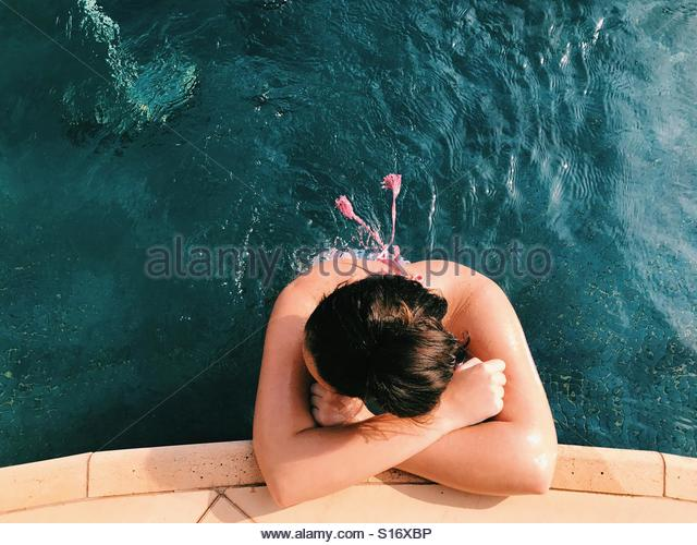 Girl relaxing in a blue pool on a sunny day - Stock-Bilder