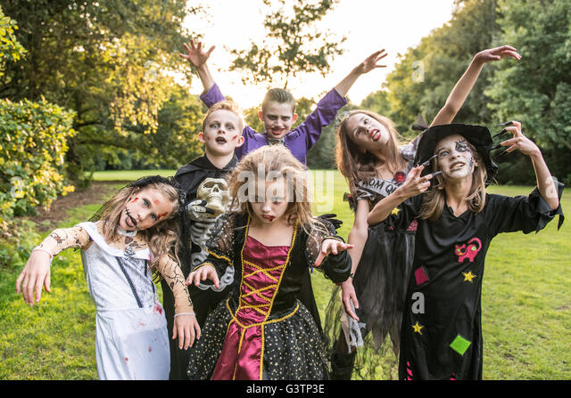 Children pose in zombie costumes for Halloween Night. - Stock Image