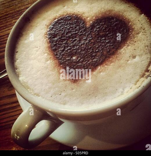 Cappuccino coffee drink in large mug and a heart shaped chocolate shape on the foam - Stock-Bilder