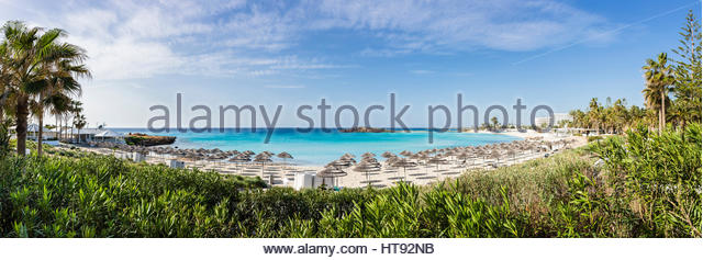 Scenic over view of Nissi Beach with beach umbrellas at the Nissi Beach Resort in Agia Napa, Cyprus - Stock Image