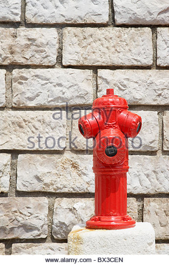 red fire hydrant in front of wall - Stock Image