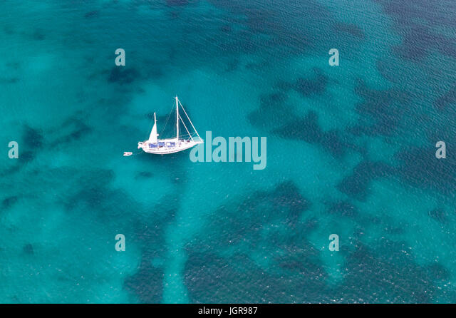 Aerial view of a little yacht on amazing beach with a turquoise and transparent sea. Emerald Coast, Sardinia, Italy. - Stock Image