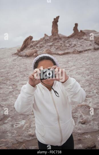 Young girl taking photograph using camera, Valley of the Moon, San Pedro, Atacama, Chile - Stock Image