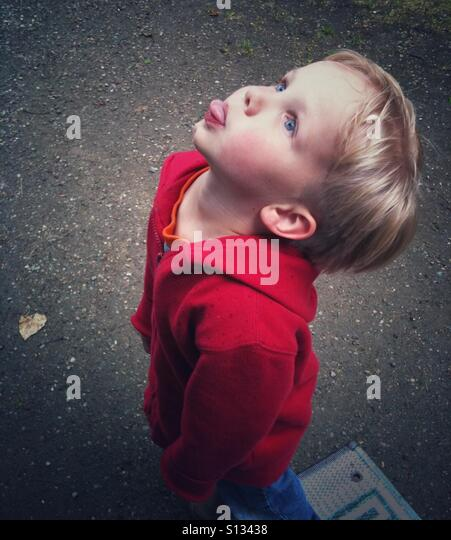 A boy sticks his tongue skyward, hoping to catch one of the first raindrops of a small storm. - Stock Image