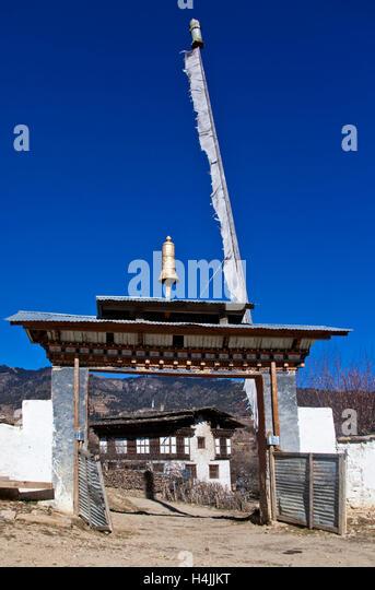 Monastery entrance framing village house, Ura, Bumthang region, Bhutan, South Asia - Stock Image