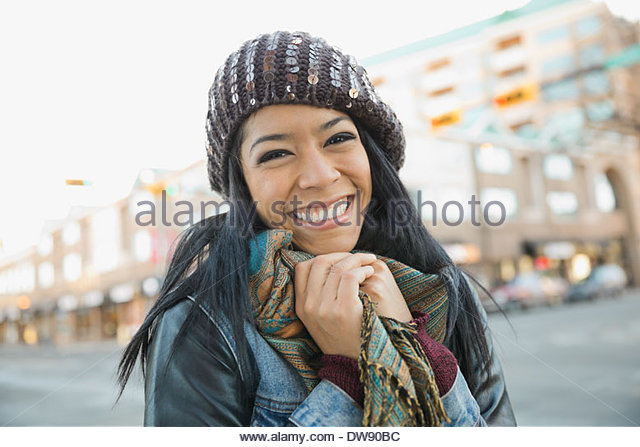 Portrait of smiling woman on city street - Stock Image