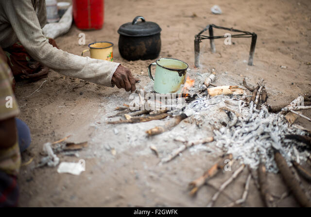 San people, or bushmen building fire in Botswana, Africa - Stock Image