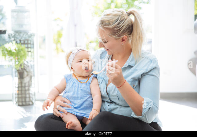 Mom feeding her baby girl - Stock Image
