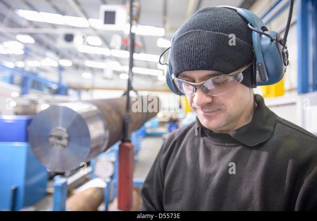 Worker wearing headphones in factory - Stock Image