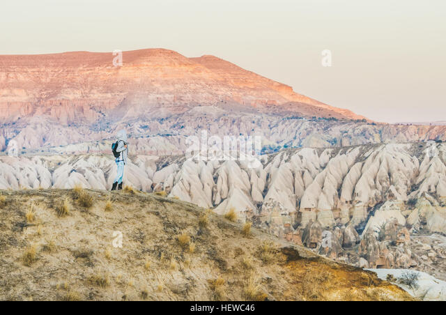 Young woman traveller hiking in mountains in Cappadocia, Turkey - Stock Image