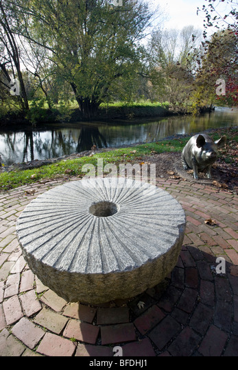 An old stone grist mill wheel and pig sculpture, outside the Brandywine River Museum, Chadds Ford, Pennsylvania, - Stock Image