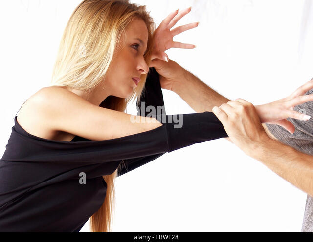 long-haired blond young woman in a violent fight with a male opponent - Stock Image