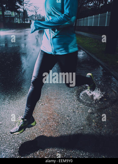 Young woman running at rainy day - Stock Image